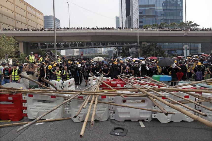 Protesters stand behind a makeshift barricade as they take part in an anti-government march in Kwun Tong, Hong Kong on Aug 24.