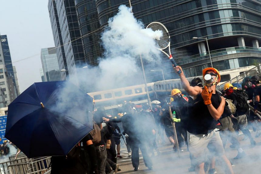 A demonstrator throws back a tear gas canister during a protest in Hong Kong on Aug 24.