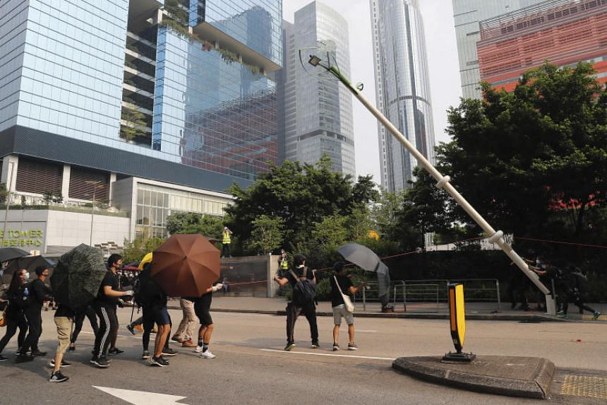 Demonstrators try to pull down a smart lamppost during a protest in Hong Kong on Aug 24.