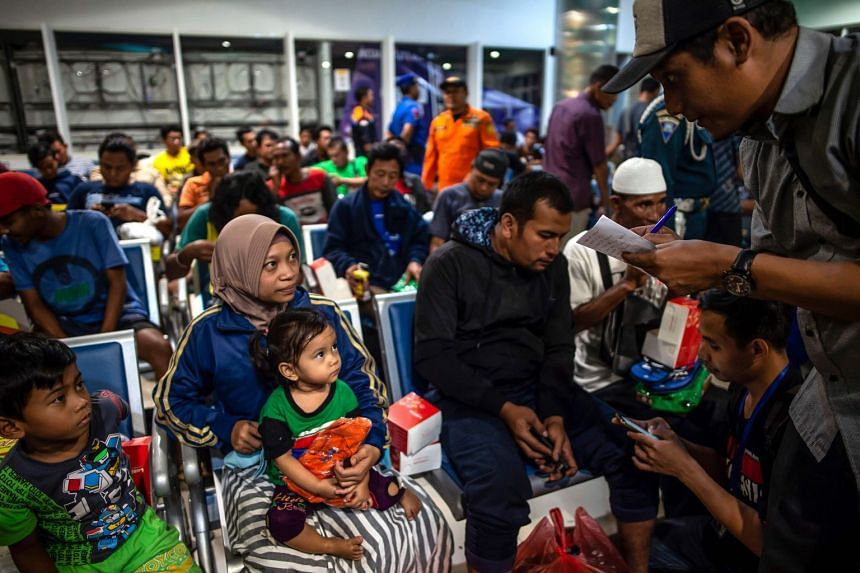 Ferry passengers gather at Tangjung Perak seaport after being evacuated.