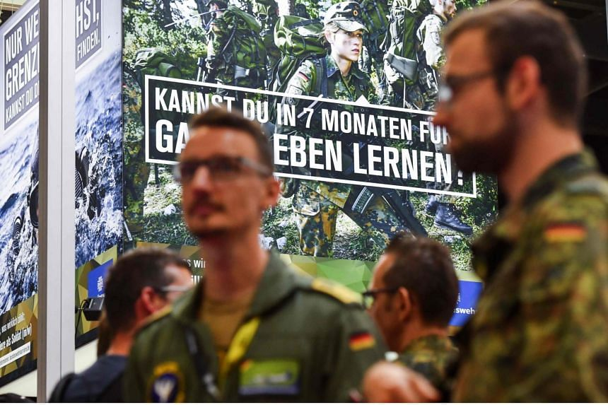 German soldiers stationed at the German Armed Forces Bundeswehr stand to recruit voluntary members at the video games trade fair, Gamescom, in Cologne, Germany, on Aug 21, 2019.