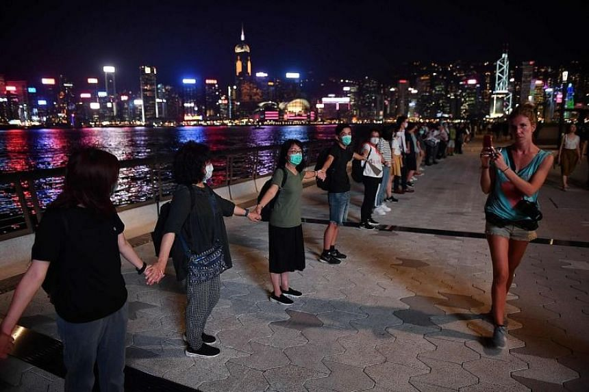 Protesters linking hands to form a human chain along Victoria Harbour in Hong Kong, on Aug 23, 2019. There have been calls for a non-cooperation campaign to jam up the transportation network to the airport on Aug 24.