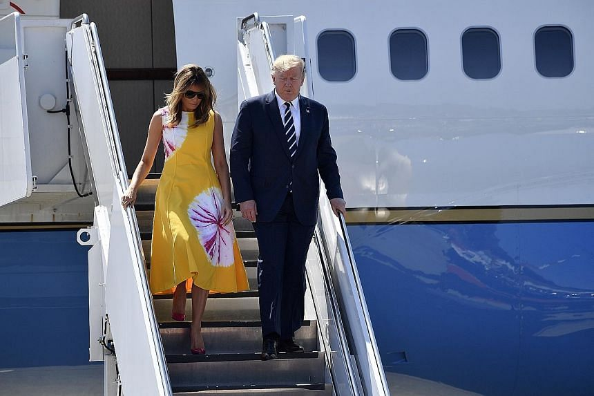 Above: US President Donald Trump and First Lady Melania Trump arriving at Biarritz airport in France yesterday. Right: Protesters holding portraits representing G-7 leaders on the summit's opening day. PHOTOS: EPA-EFE
