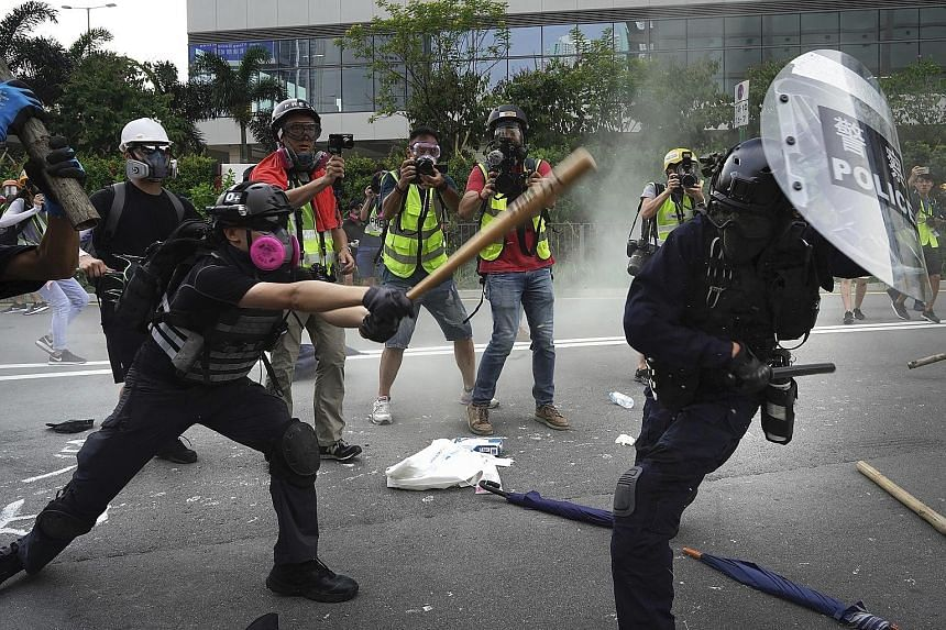 Violence erupted during anti-government protests in Hong Kong yesterday as protesters and riot police exchanged Molotov cocktails and tear gas, after a week of relative calm. Amid concerns that the authorities could potentially use technology to iden