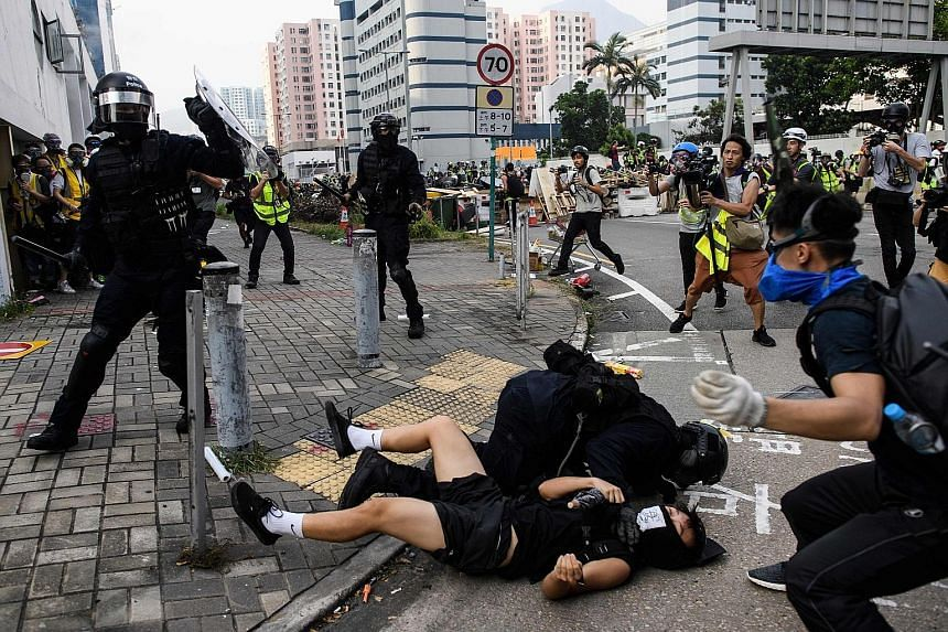 Hong Kong riot police yesterday clashing with protesters, who retaliated with a barrage of stones, bottles and bamboo poles, as a stand-off descended into violence.