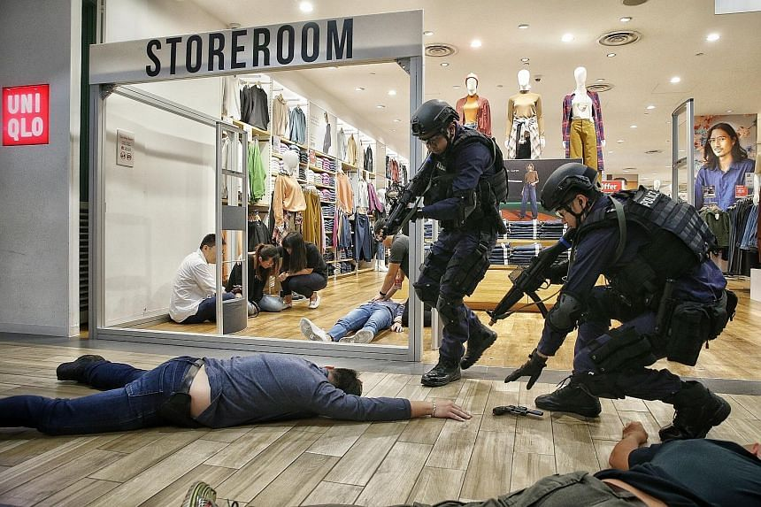 Singapore Police Force and Singapore Civil Defence Force officers responding to a simulated terror attack at the SGSecure roadshow at Northpoint City shopping mall yesterday.