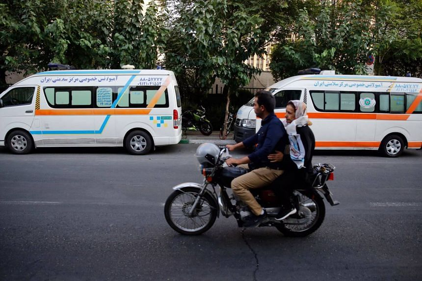 In a photo taken on Aug 22, 2019, an Iranian couple drive a motorbike past private ambulances in Teheran, Iran. Emergency service vehicles are allowed to run through red lights and have a clear path to their destinations, in one of the world's worst