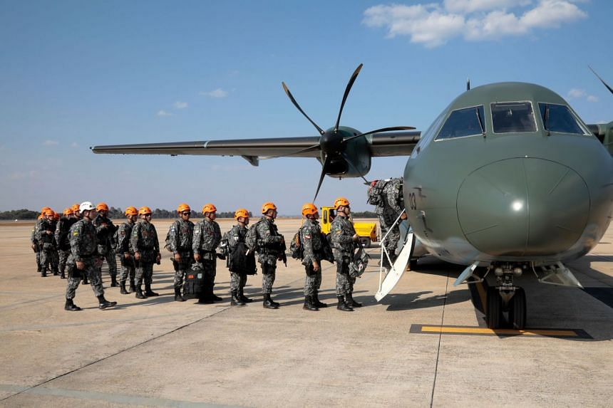 National Force military firefighters stand in line to board a plane to help fight fires in the Amazon rainforest.