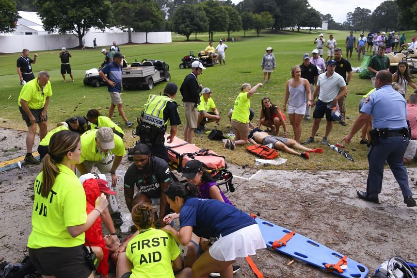 Spectators are tended to after a lightning strike on the East Lake Golf Club course.