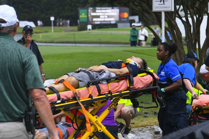 A spectator is taken to an ambulance after a lightning strike on the course.
