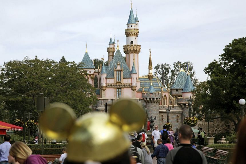 In a 2015 photo, visitors walk towards Sleeping Beauty's Castle (background) at Disneyland.