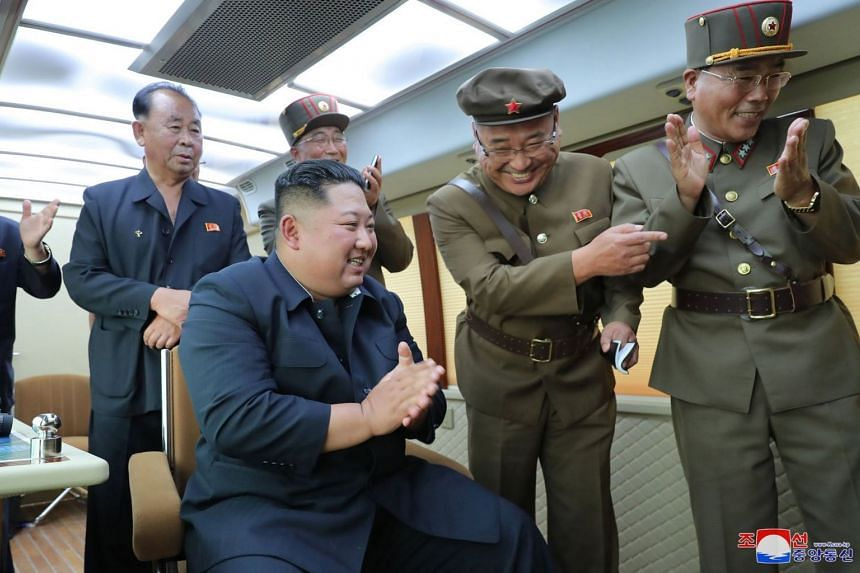 A photo provided by KCNA on Aug 17, 2019 shows Kim applauding the test-fire of a new weapon.