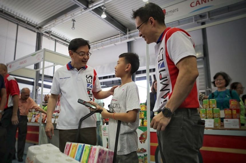 Deputy Prime Minister Heng Swee Keat (left) and Mayor of North-East District Desmond Choo (right) interacting with Javier Chee, 11, at the launch of Tampines Project 100=50 at at Arena@OTH on Aug 25, 2019.