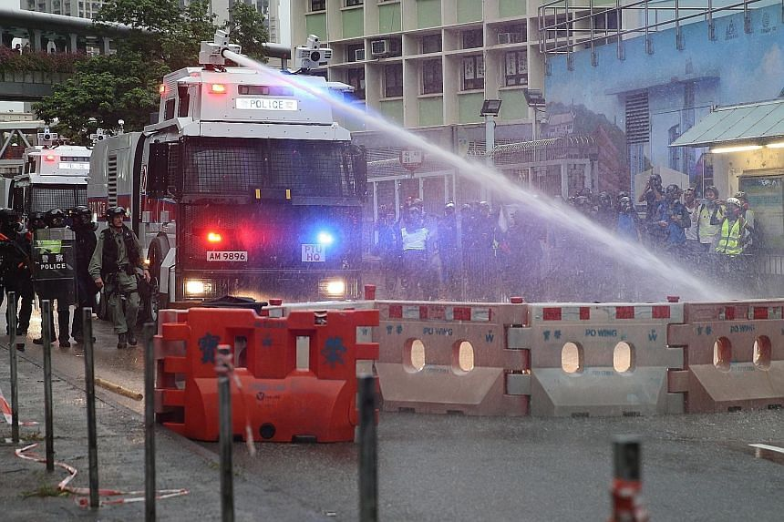 An anti-riot police vehicle equipped with a water cannon clearing the road of a barricade set up by protesters in Kwai Fong and Tsuen Wan, in Hong Kong. Traffic was paralysed after hundreds of black-clad protesters put up barricades made of dismantle
