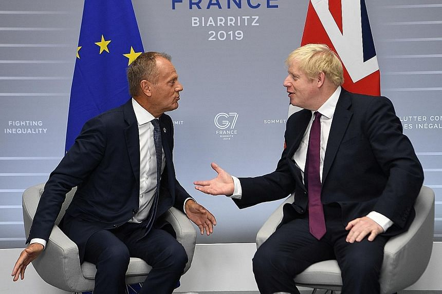 European Council President Donald Tusk (left) and British Prime Minister Boris Johnson at a bilateral meeting during the Group of Seven summit in Biarritz yesterday. Uncertainty over Brexit has roiled markets.
