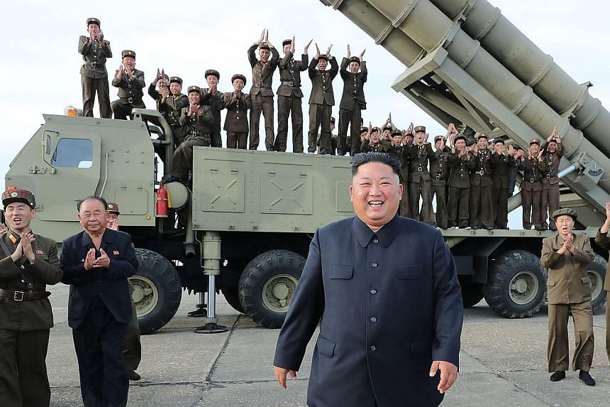 """North Korean leader Kim Jong Un at the test-firing of a """"super-large multiple rocket launcher"""" last Saturday. US President Donald Trump said he was """"not happy"""" about the missile test but played down its seriousness."""