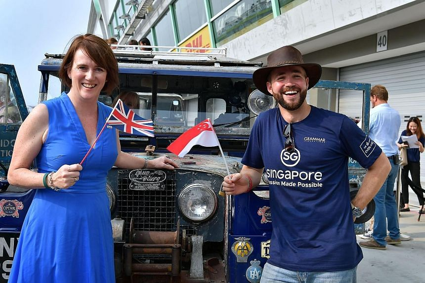 British High Commissioner to Singapore Kara Owen with British film-maker and TV presenter Alex Bescoby, who is taking part in the overland drive from Singapore to London, at the F1 Pit Building yesterday.