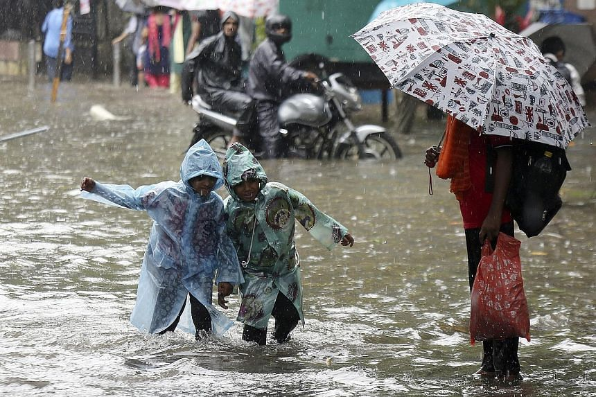 Children wading through a flooded street in Mumbai earlier this month. Home to nearly 22 million people, the financial capital of India is demanding more durable fixes to its flooding problem from policymakers.