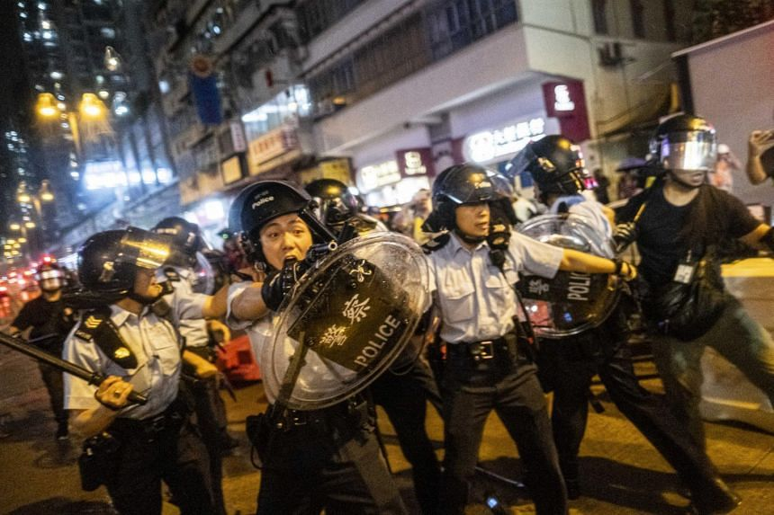 A police officer in riot gear aims a gun at protesters during a clash in the Tsuen Wan district of Hong Kong, on Aug 25, 2019.
