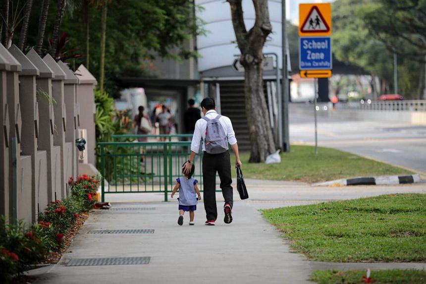 A father walking with his daughter to school.