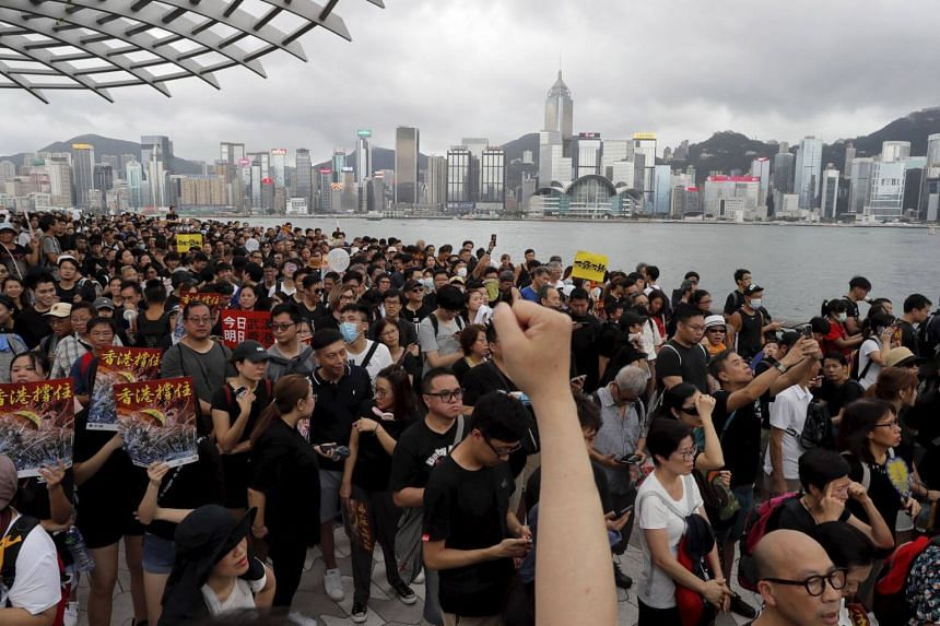 Protesters marching as the skyline of Hong Kong is seen in the background, on July 7, 2019.