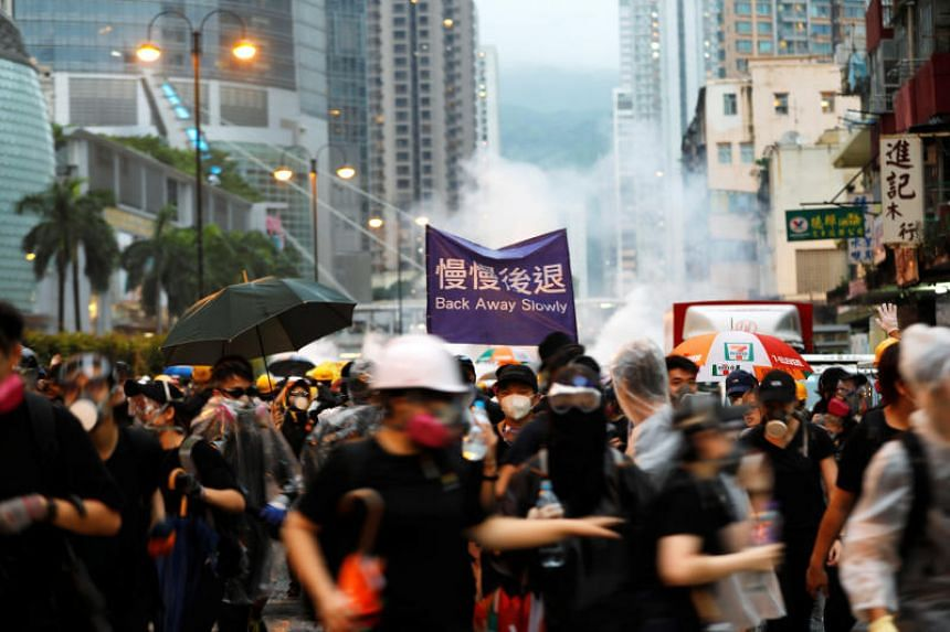 Protesters run as riot police fire tear gas during a protest in Hong Kong on Aug 25, 2019.