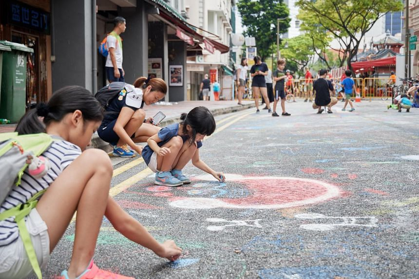 """In a photo taken on May 27, 2018, children draw on the road at the """"Walk the Chalk"""" event, held along Telok Ayer Street between Boon Tat Street and Cross Street as part of Car-Free Sunday SG."""