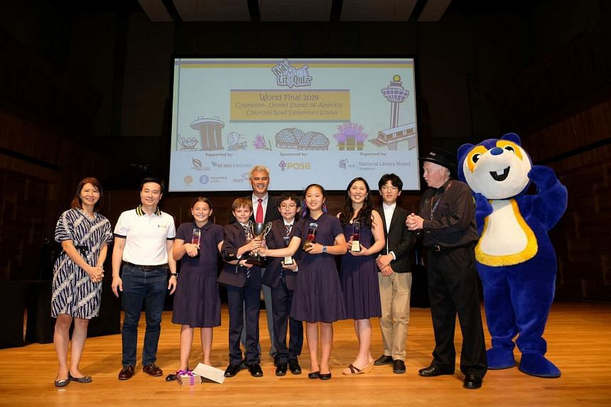 Ms Catherine Lau, Assistant Chief Executive, Public Library Services, NLB, Mr Shee Tse Koon, Singapore Country Head, DBS, and Mr Wayne Millls, the Quizmaster and the creator of Kids' Lit Quiz with the winning team from Churchill Road Elementary Sch