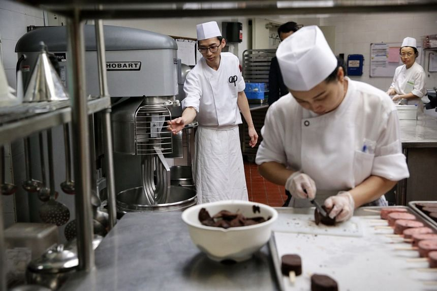 An employee (left) using a metal guard installed on a dough mixer while another exhibits safe knife skills in the pastry kitchen of the Regent Singapore hotel on Aug 26.