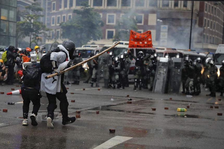 Protesters use bamboo sticks as they face riot police during a protest in Hong Kong on Aug 25, 2019.