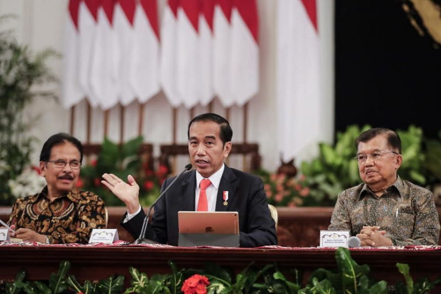Indonesian President Joko Widodo, accompanied by his vice-president Jusuf Kalla (right) and Minister of Agriculture and Land Planning Sofyan Djalil, announces the location of the country's new capital city during a press conference in Jakarta on Aug