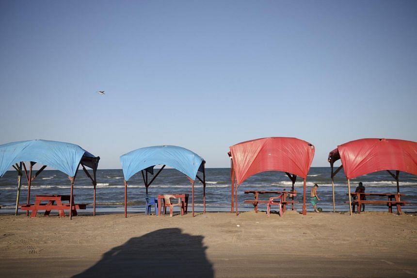 Picnic tables shaded by tarps line the shoreline in Playa Bagdad close to the mouth of the Rio Grande near the border city of Matamoros, Mexico.