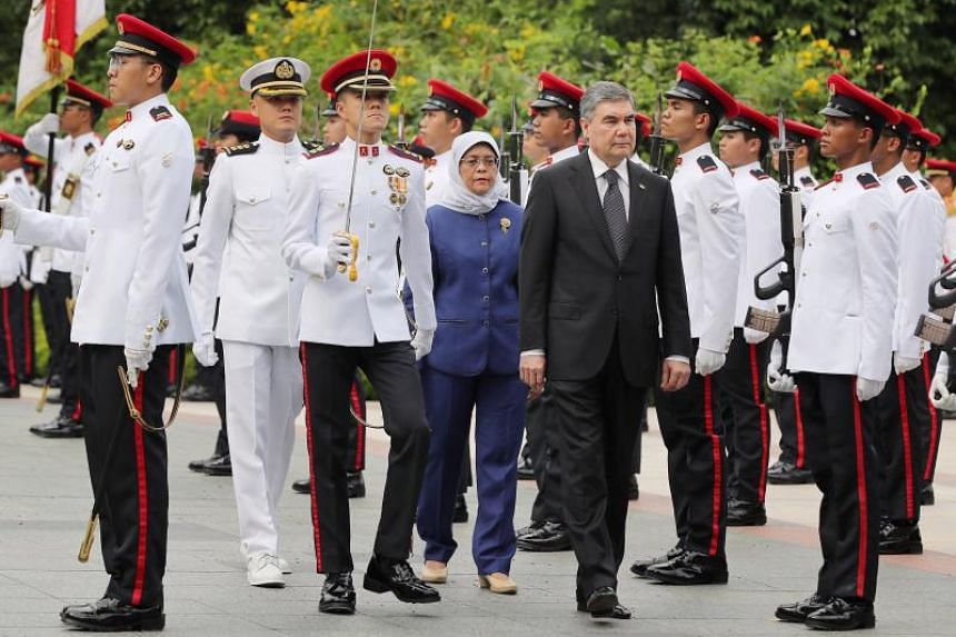 Turkmenistan President Gurbanguly Berdimuhammedow reviewing the guard of honour with President Halimah Yacob at the Istana on Aug 27, 2019.