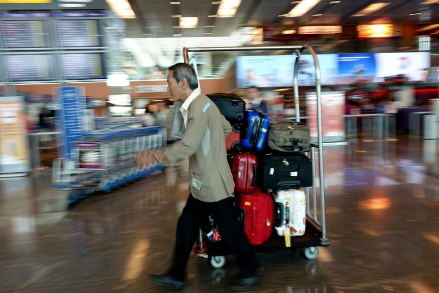 A porter manouvers a cart loaded with luggage at Changi Airport Terminal 1.