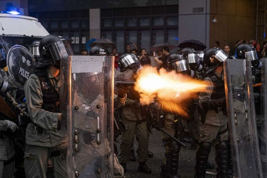 A police officer in riot gear fires tear gas at protesters during a clash in the Tsuen Wan district of Hong Kong, on Aug 25, 2019.