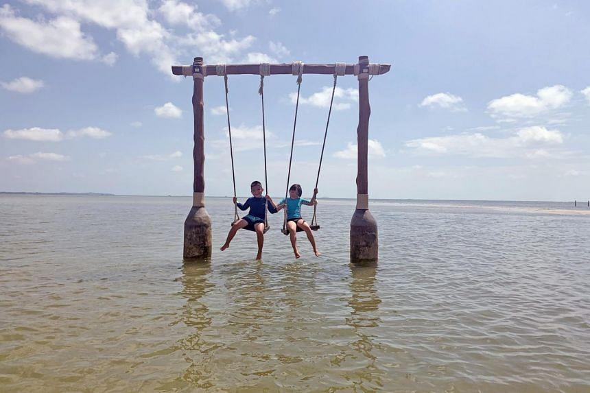 Jon Chia, seven, and Michela Chia, 10, on the sea swing at The Residence, Bintan.