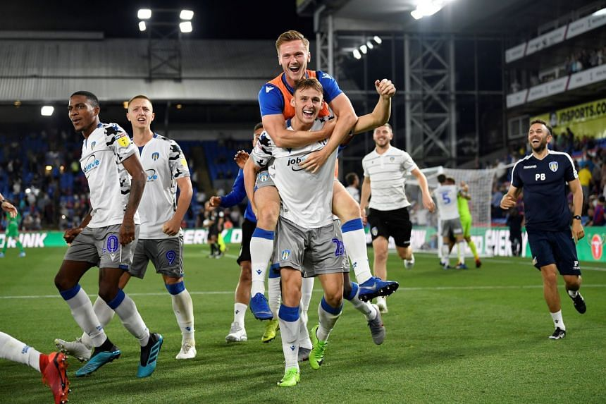 Colchester United players celebrate defeating Crystal Palace.