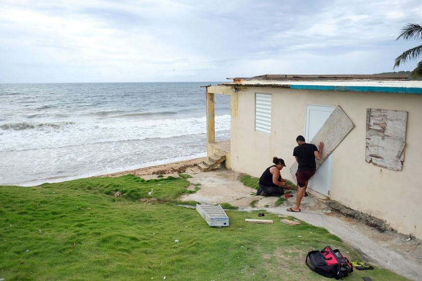 A couple boards up the door of their beachfront house as Tropical Storm Dorian approaches in Yabucoa, Puerto Rico.