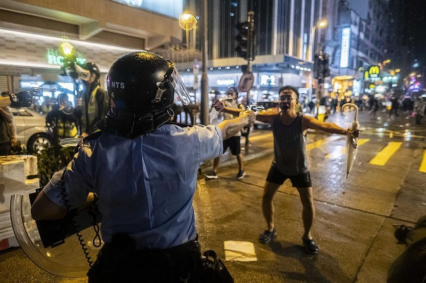 A police officer drawing a pistol on a protester during a rally in Hong Kong on Sunday, amid escalating tensions in recent weeks.