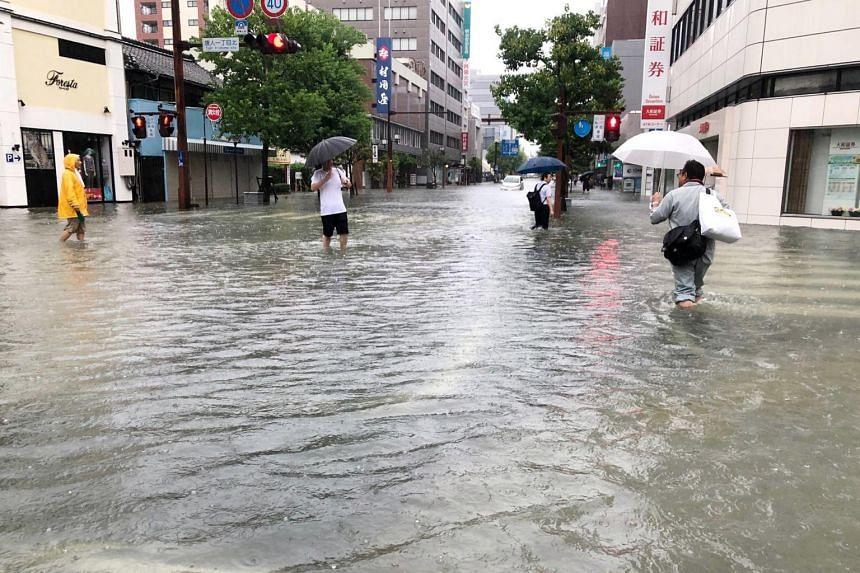 People walk in a flooded street near Saga station in Saga, Saga prefecture, south-western Japan, on Aug 28, 2019.