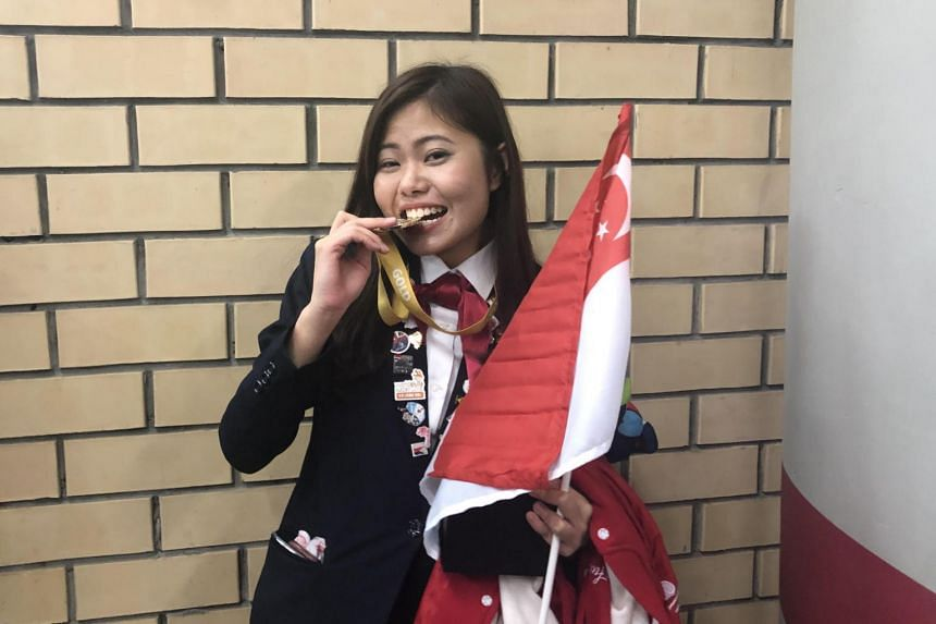 Nanyang Polytechnic nursing graduate Regina Chia, 20, with her gold medal at the 45th WorldSkills Competition closing ceremony on Tuesday night (Aug 27).