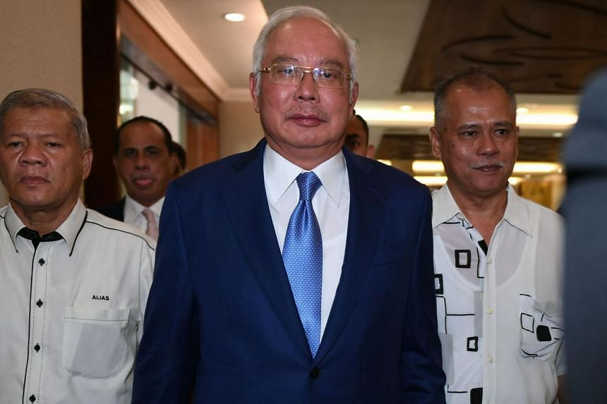 Malaysia's former prime minister Najib Razak (centre) has maintained that he is innocent and dismissed the charges as politically motivated