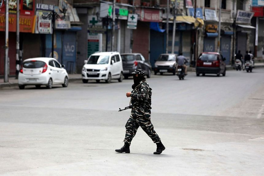 An Indian paramilitary soldier walks near a closed market in Srinagar.