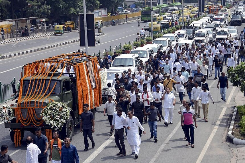 The funeral procession (above) of former Indian finance minister Arun Jaitley in New Delhi on Sunday.