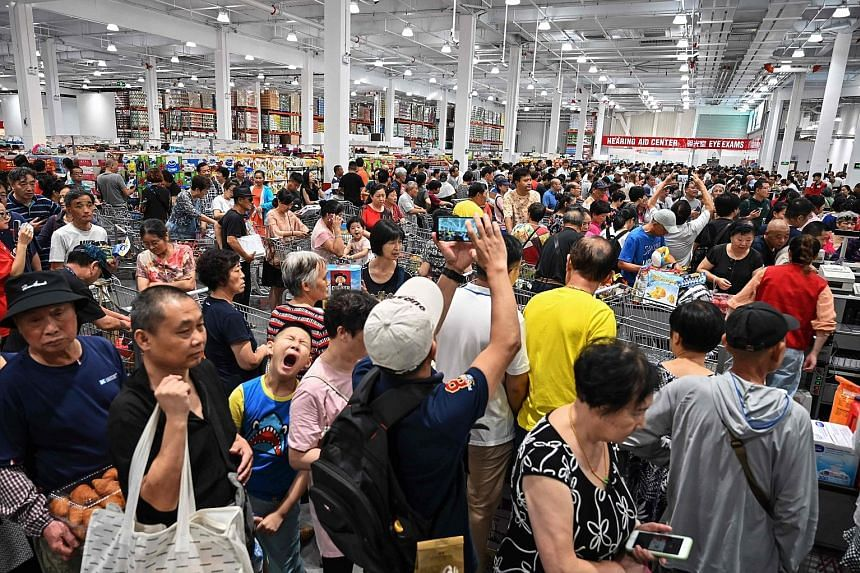 Above: People jostling to get roast chicken at the first Costco outlet in China, which opened on Tuesday. Right: Large crowds had flocked to the store in Shanghai forcing the US retailer to close early on the opening day.