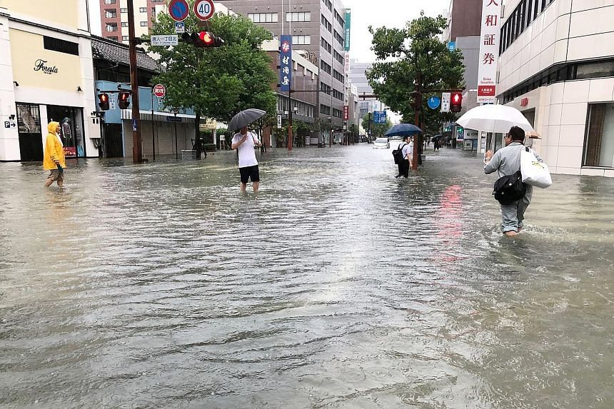 People wading through floodwaters in Saga city, Japan, yesterday. The authorities said they received multiple reports of houses flooded in Saga prefecture.