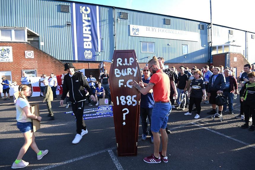 Bury Football Club supporters carrying a mock coffin outside their Gigg Lane stadium. The League One club, two-time winner of the FA Cup, has been expelled from the English Football League over financial insolvency. PHOTO: EPA-EFE