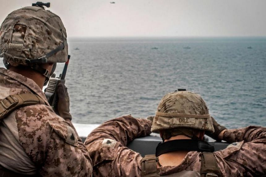 US sailors aboard an amphibious transport dock ship keep watch on Iranian fast inland attack crafts in the Strait of Hormuz.