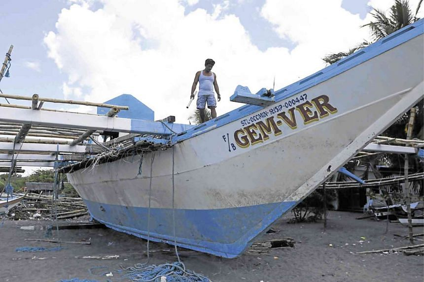 In a photo taken on June 18, 2019, fishing boat skipper Junel Insigne inspects his damaged FB Gem-Ver 1 vessel, which was hit by a Chinese trawler.