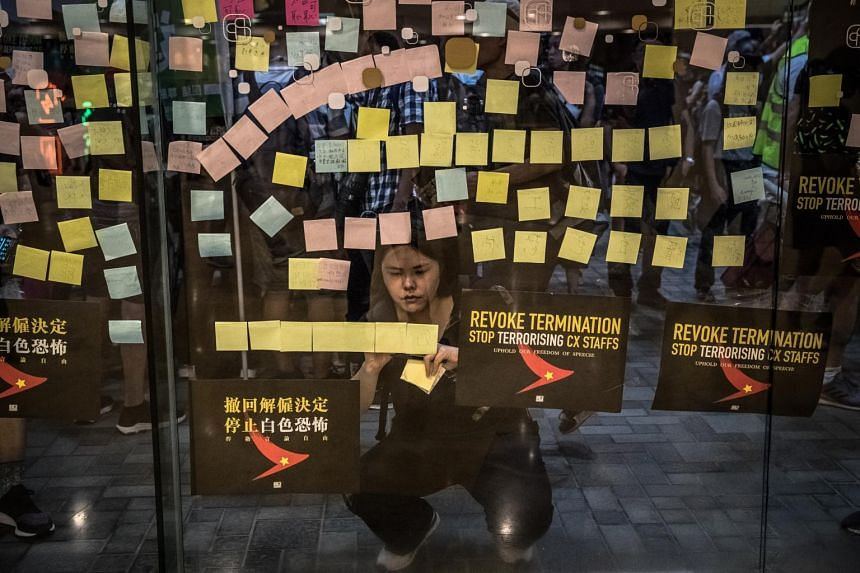 A protester places stickers outside a shopping mall during a rally to denounce recent firings at airline Cathay Pacific, in Hong Kong on Aug 28, 2019.